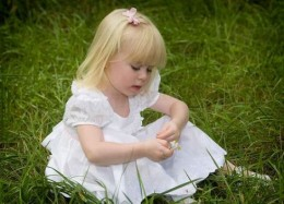 Grandness of the world shown in a little blond girl in a white dress and pink bow