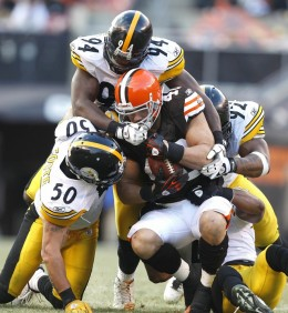 Peyton Hillis being tackled by several members of the Pittsburgh Steelers.