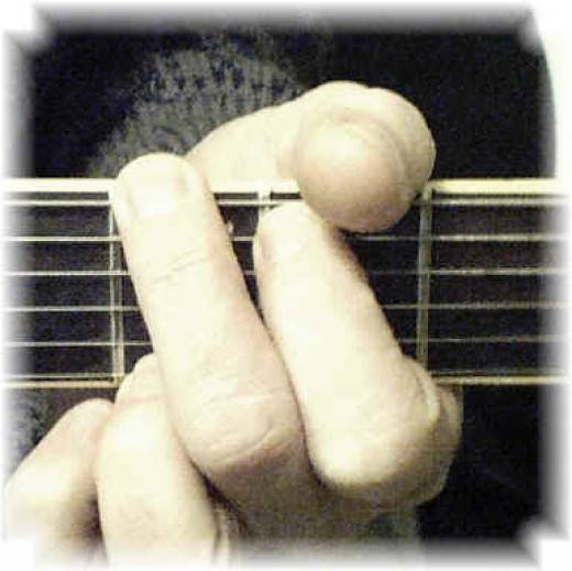 G chord being fingered on the guitar