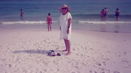 My mother walking on the white sand at Fort Walton Beach