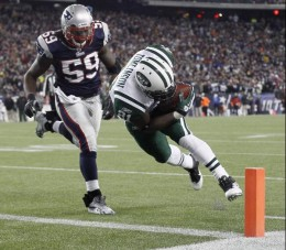 New York Jets running back LaDainian Tomlinson (21) scores a touchdown in front of New England Patriots linebacker Gary Guyton (59) during the first half of an NFL divisional playoff football game in Foxborough, Mass., Sunday, Jan. 16, 2011. (AP Phot