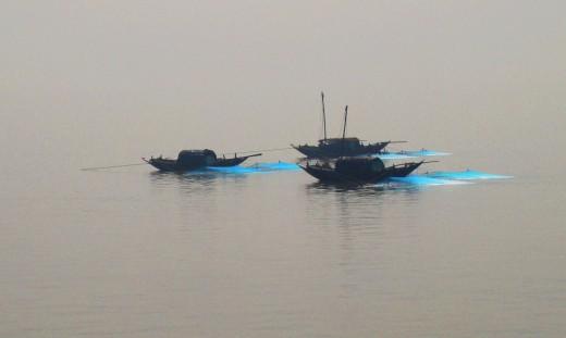 Three boats with fishing net in Ganga
