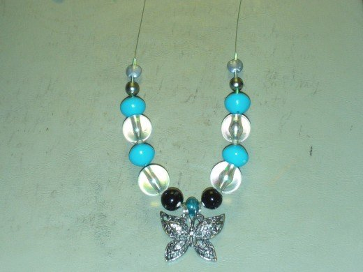 Add another small cylinder glass bead to each side of the necklace.