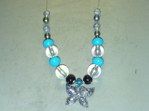 Here I have added two light silver fake pearl beads; one to each side of the necklace.  These beads are round and flat.