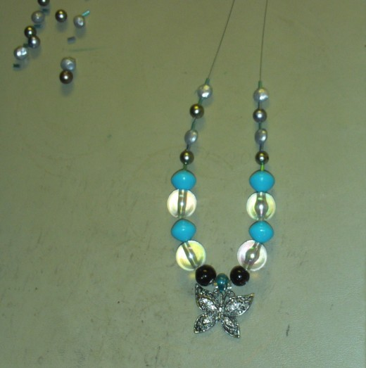 Added another small cylinder glass bead to each side of the necklace.