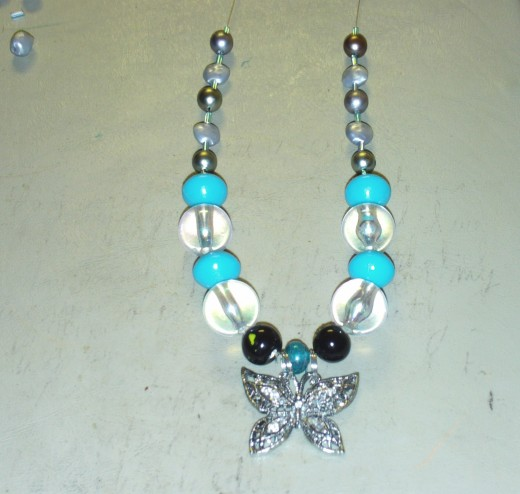 Add another cylinder glass bead to each side of the necklace.