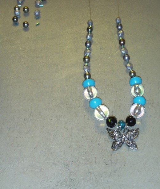 I added a round and flat light silver fake pearl bead to each side of the necklace.