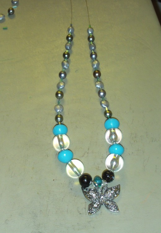 So I continue the pattern up both sides of the necklace with the dark silver, cylinder glass bead, and light silver bead.