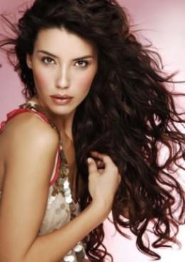 Dark hair intensifies a beautiful face as a fine frame surrounds a work of art.