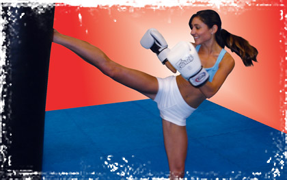 Beautiful brunette in white shorts and boxing gloves with a high shoulder height kick.