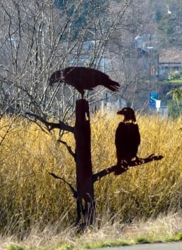 Steel metal eagles sitting on metal tree snag.
