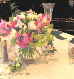 Glass beads and tiny orchid blooms scattered around the centerpiece.
