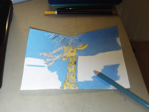 I began to use the cerulean blue colored pencil to carefully color around the giraffe.