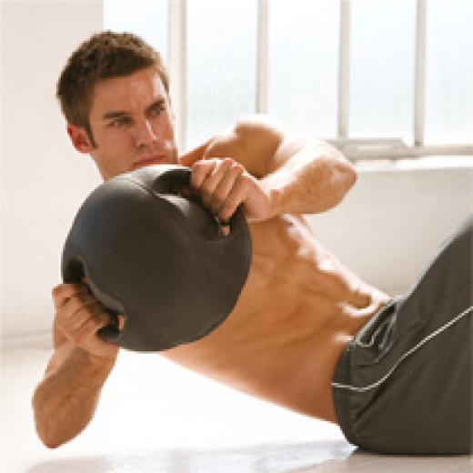 male with dark grey medicine ball with handles