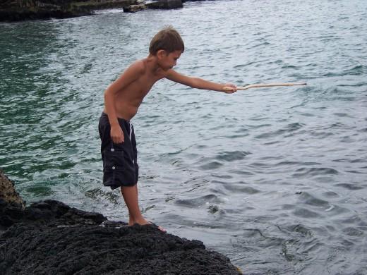 A cute little Hawaiian boy fishing with a stick.