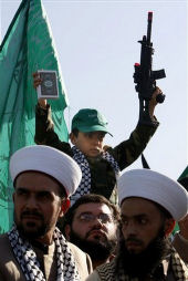 A small child waiving a gun and the Koran. Not exactly an American custom.