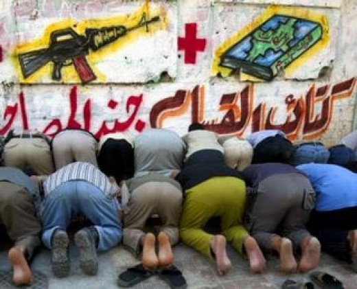 Mulims in prayer before banner of the Koran and a weapon.