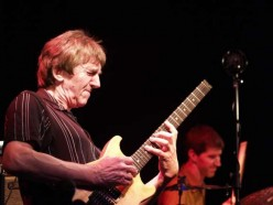 Jazz Fusion virtuoso and living legend, Allan Holdsworth. He raised the standard as well as the strap height.