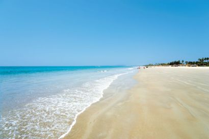 Pristine, crystal clear waters lap gently onto a Goan beach.