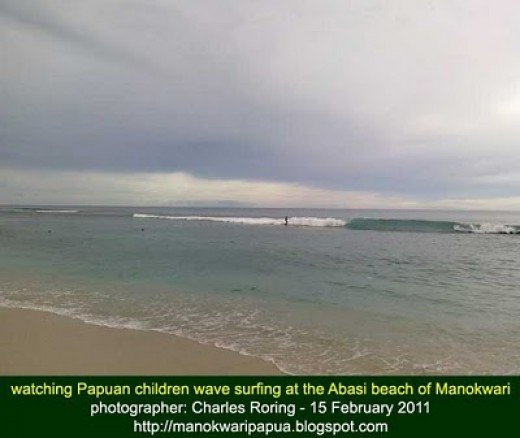 photo of Papuan children wave surfing taken with my cell phone camera that does not have optical zoom device