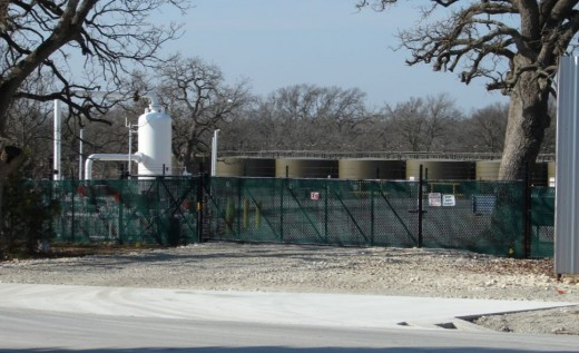 Behind the white fence is this gas distribution/ waste water storage site on what was a residential lot.