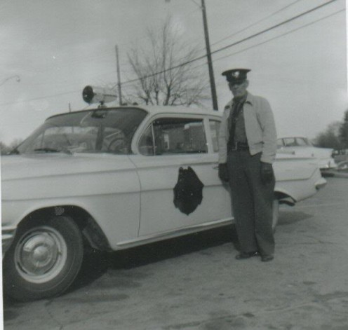 Henry Harris - Town Marshal for the town of Elvins in St. Francois County, Missouri. Photo taken in 1960 next to his new 1961 patrol car.