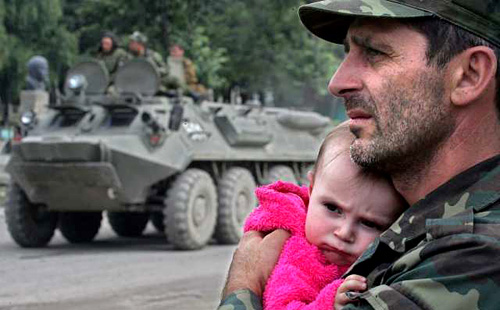 Dmitry Kostyukov AFP/Getty Image A South Ossetian military man holds a child as he looks at an armored vehicle in the village of Dzhava, South Ossetia, Georgia.