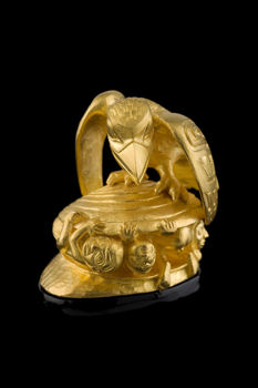 Raven encourages the first men to creep out of the clamshell. Small golden sculpture.