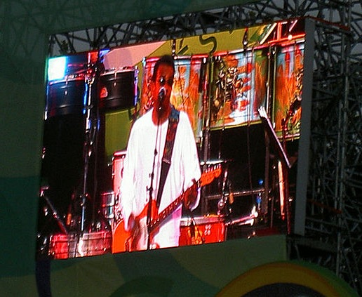 Jorge Ben Jor on the big video screen during a Paris performance.  Photo by Alex de Carvalho, courtesy Flickr and Wikimedia Commons.