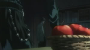 Ryuk stands by the bowl of apples. Light stands in the background.
