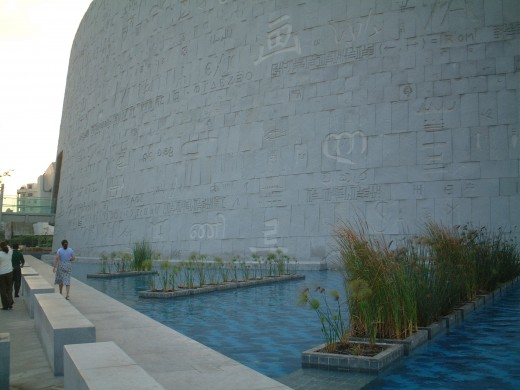 The water surrounds the whole building. The wall with its symbols and letters from some 120 languages.