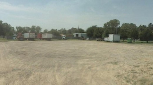 An open gravel lot is the storage spot for the decendents of the founder of Joyland. Their traveling carnival serves much of the central US during the warm months.
