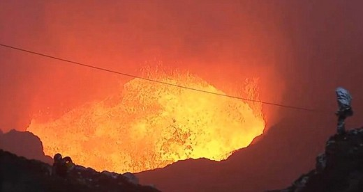 Volcano abseiling:  A daredevil stands inside the crater as hot lava spews below