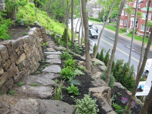 Natural stone retaining wall. The third tier in this backyard garden leading down to a busy boulevard. Gardens soften the look of the multiple stone walls.