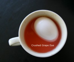 An egg soaking in a dye made from crushed grapes.