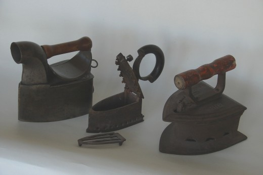 """(L) Coal Iron with funnel. (C)Dainty Charcoal iron showing internal grate. (R) Iron from India, still used by street """"Iron Wallas'."""