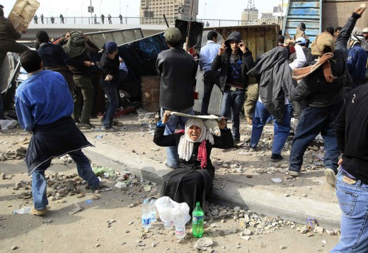 A woman opposition supporter takes shelter while providing water during rioting with pro-Mubarak demonstrators near Tahrir Square in Cairo February 3, 2011