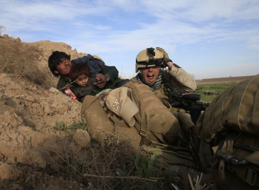 U.S. Marine Lance Corporal Chris Sanderson, 24, from Flemington, New Jersey shouts as he tries to protect an Afghan man and his child after Taliban fighters opened fire in the town of Marjah, in Nad Ali district, Helmand province, February 13, 2010.