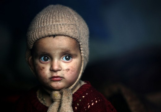 A little girl who is an earthquake survivor sits inside a tent at a camp in the devastated city of Muzaffarabad November 24, 2005.
