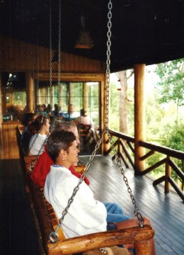 People seated on the rustic porch of Grandlake Lodge.