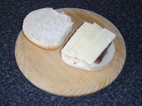 Slices of cheddar cheese are laid atop the Lorne sausage