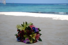 My bouquet of stunning fresh flowers lying on the white sands of a Grand Cayman beach.