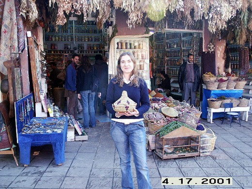 Apothecary on the background. I am holding a tajin shaped basket thing that we use at home to keep tortillas warm. Marrakesh, Morocco.