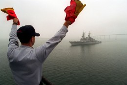 Navy Signalman communicates to oncoming ship