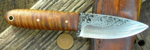 A custom hand forged carry knife with tiger maple handle.