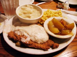 A plate of Cracker Barrel chicken with their delicious gravy, mashed potatoes, mac n' cheese and apple slices.