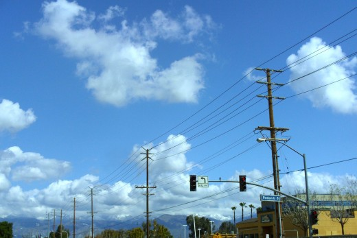 Clouds above the traffic lights and telephone wires.