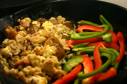 scramble the eggs and let the peppers cook a little beside them