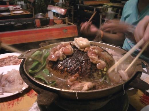 Mookata cooking over a hot coals.