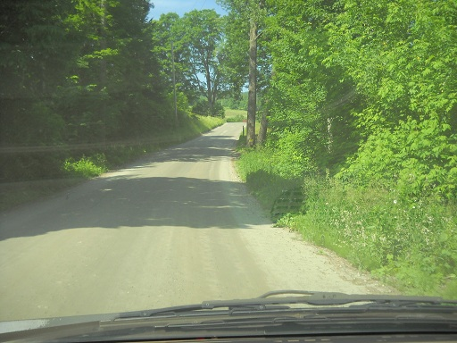 Vermont still has miles and miles of dirt roads with lush green trees and plants growing on either side.